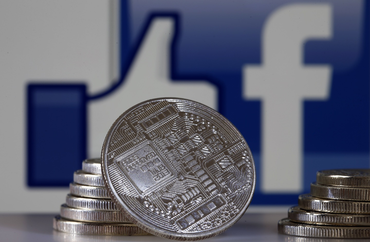 Facebook is becoming a bank with new cryptocurrency Libra. Iconic Facebook and thumbs up icon next to hypothetical bitcoins.