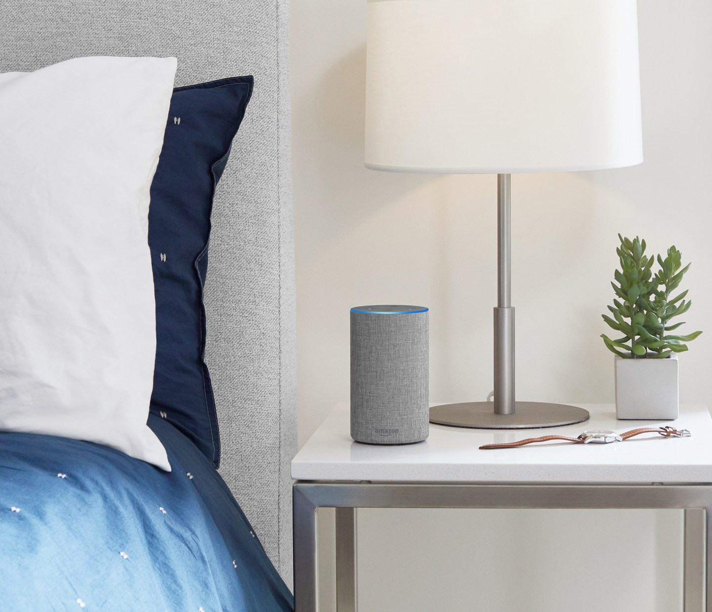 A grey Amazon Echo sits atop a nightstand