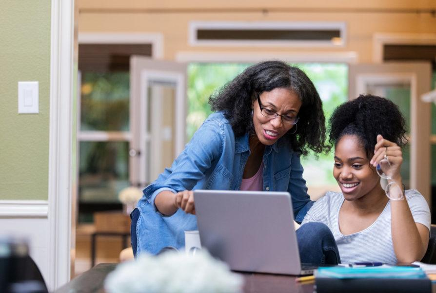 Confident mature African American mom helps her young adult daughter study for a college exam.
