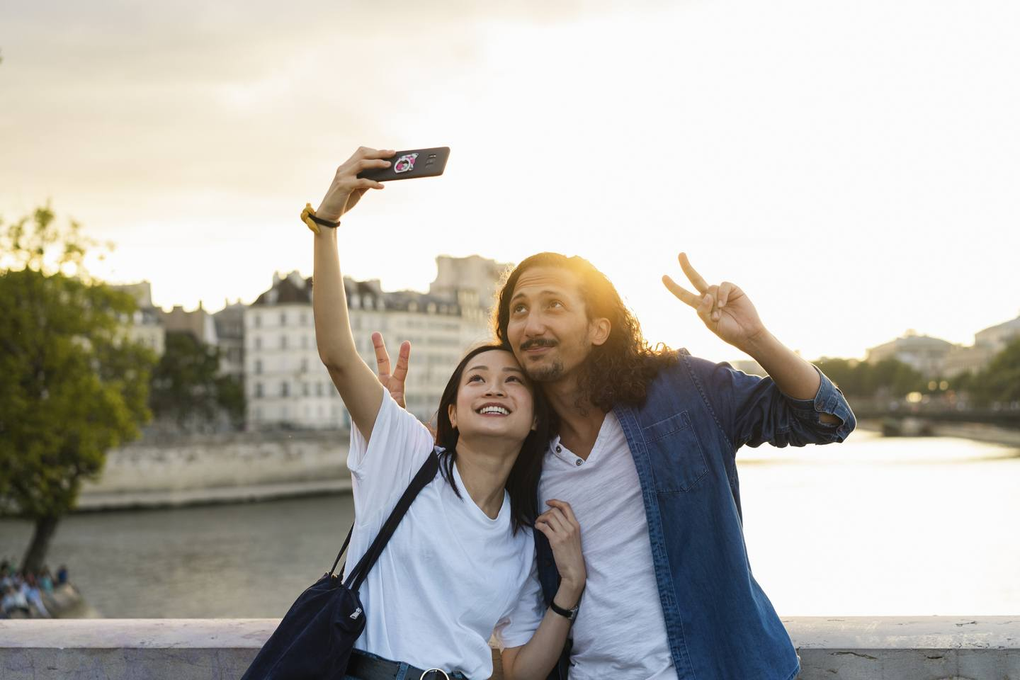 two people posing for a selfie on the bridge overlooking a river