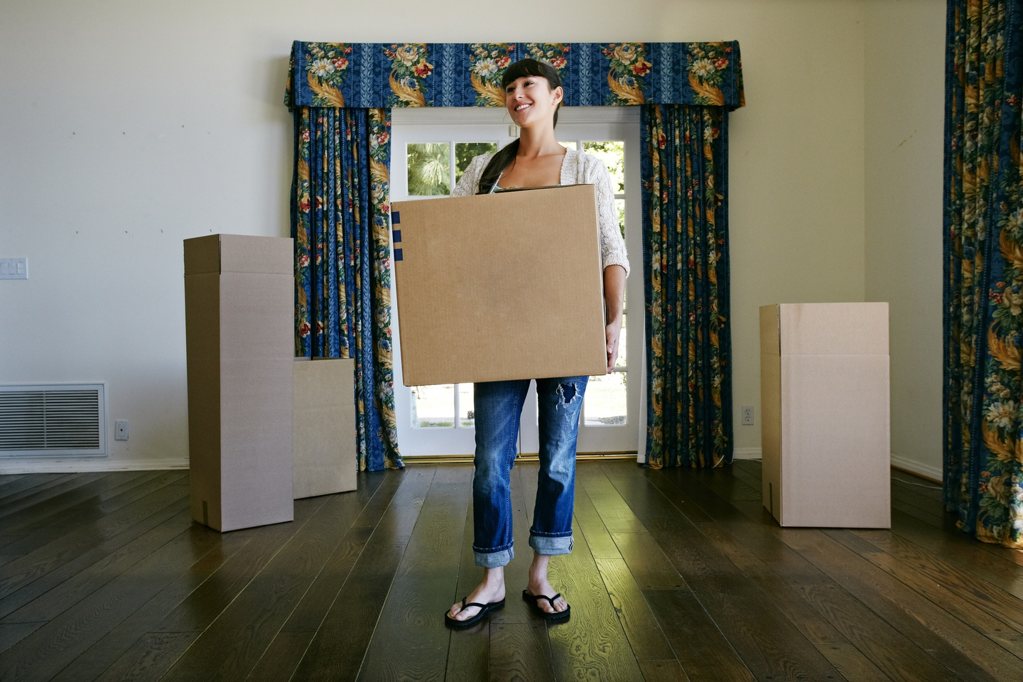 a woman holding a packing box and standing in an empty house getting ready to move in