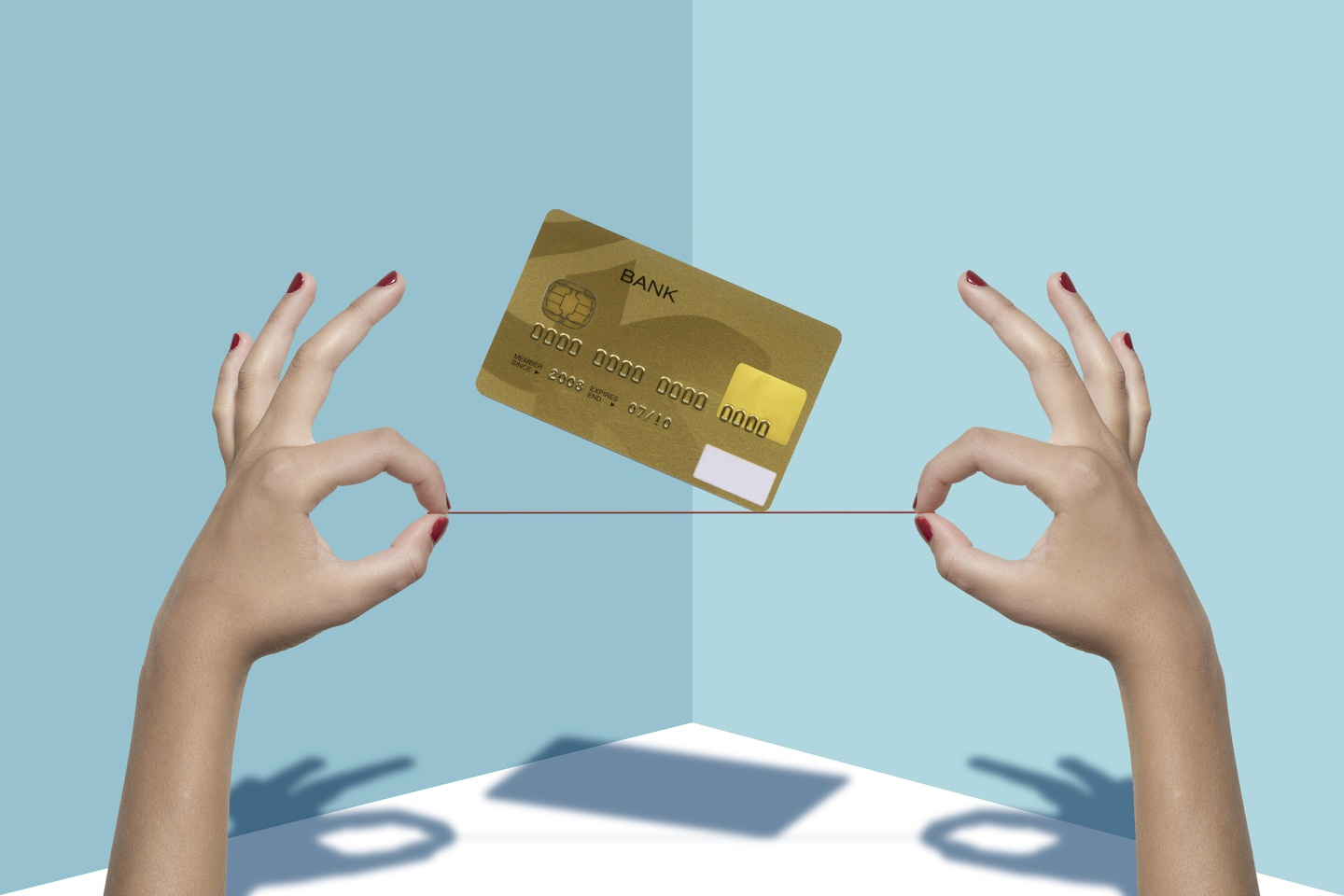 Woman's hands hold a Credit Card balanced on a thread