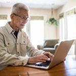 Senior man using laptop computer at home
